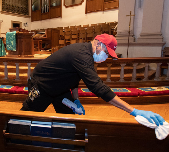a person cleaning table with sanitizer