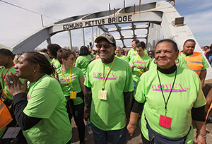 "United Methodist Bishop Woodie W. White (center) crosses the Edmund Pettus Bridge in Selma, Ala., during the 50th anniversary observance of the ""Bloody Sunday"" protest march seeking voting rights for African Americans. White brings students from his Candler School of Theology class on race relations to Selma each year. He is joined by his wife Kim (right), Ruby Shinhoster of the Southern Christian Leadership Conference's Women's Organizational Movement for Equality Now (left) and Candler student Beth Clark. Photo by Mike DuBose, UMNS"
